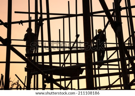 worker working on scaffold near sunset - stock photo