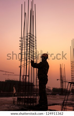 worker working with concrete iron near sunset - stock photo