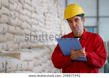 Worker Writing on Clipboard in Warehouse. Warehouse worker at work. Worker in distribution warehouse beside big pile of sacks. - stock photo