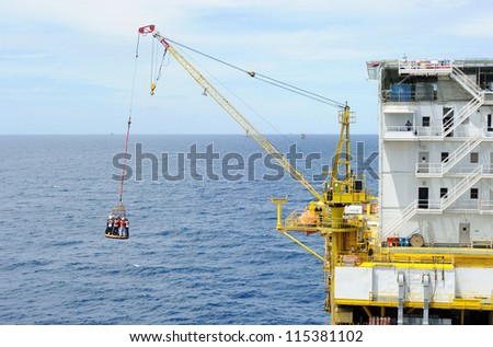 Workers are lifted by the crane to the offshore platform - stock photo