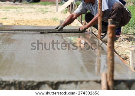 Workers are plastered concrete in the sun. - stock photo