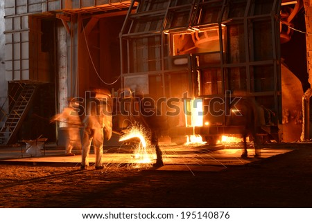 Workers are working in metal smelting workshop   - stock photo