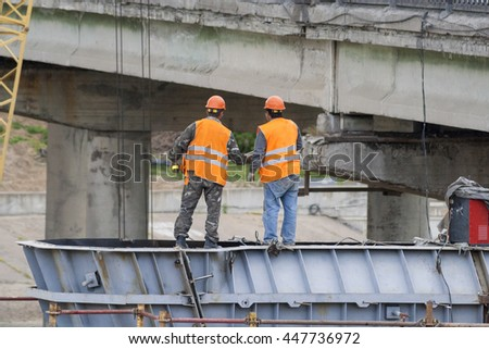 Workers assemble the bridge structure,Engineers discussing work plan. - stock photo