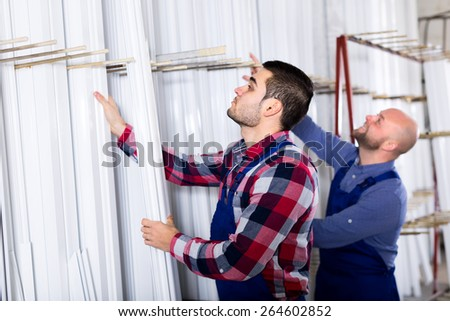 Workers at a warehouse are choosing a PVC profile - stock photo