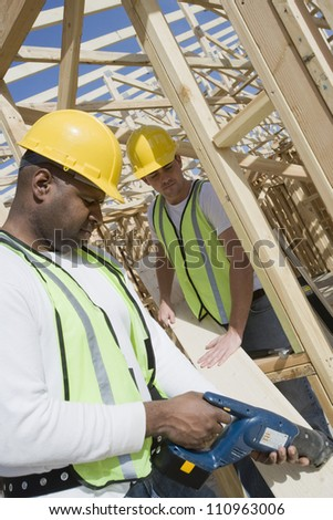 Workers at construction site working - stock photo