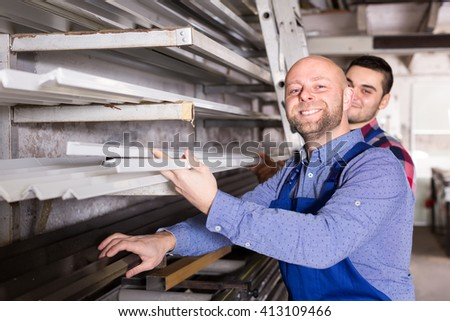 Workers at PVC window factory are taking profiles from a rack - stock photo