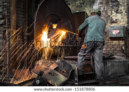 Workers at the factory cut the steel - stock photo