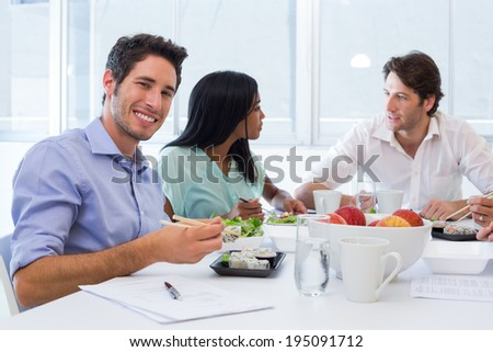 Workers chat and smile to camera while enjoying lunch in the office - stock photo