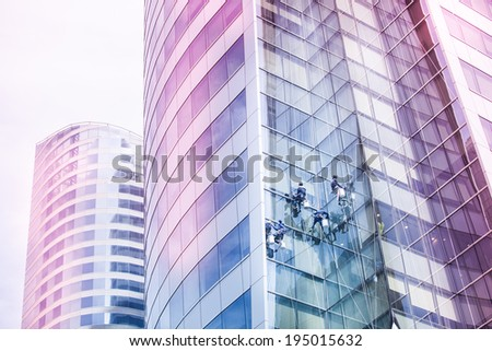 Workers cleaning windows of a tall building - stock photo