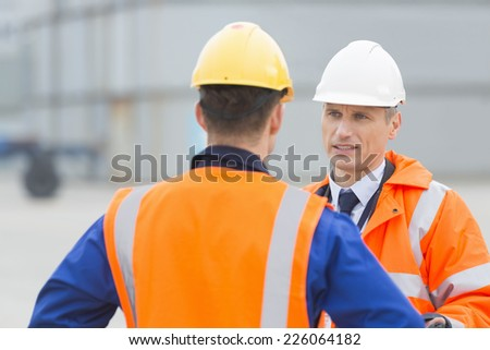 Workers conversing in shipping yard - stock photo