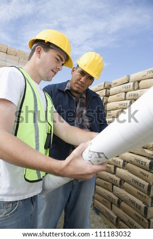 Workers discussing over a blueprint