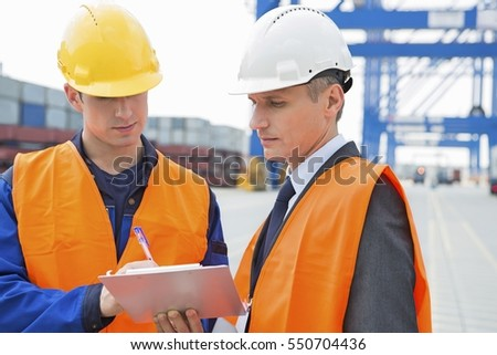 Workers discussing over clipboard in shipping yard