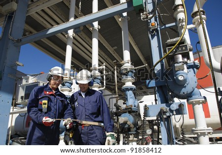 workers, engineers, in front of refinery main pipeline and filling station, typical scene inside refinery. - stock photo