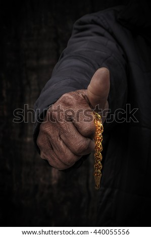 Workers hand holding gold in the darkness