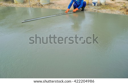 Workers hand using trowel with wet concrete, Construction road with cement.