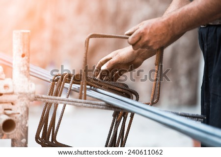 workers hands using steel wire and pincers to secure rebar before concrete is poured over it. Selective focus on center portion of image. Construction site worker , closeup hands , form work  - stock photo