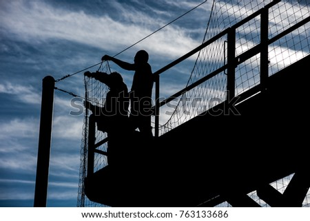 Workers hang a net that keeps balls from exiting a playing field.