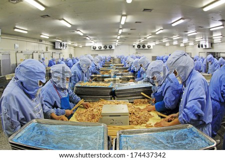 Workers in a meat processing production line, in a food processing enterprise, on December 20, 2013, tangshan city, hebei province, China.   - stock photo