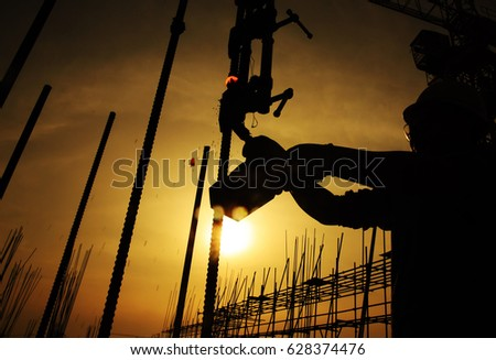 Workers in the sunset welding steel bars, concrete preparation for the preparation of real estate development projects. Busy construction site.