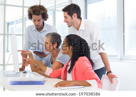 Workers looking at a presentation on the computer in the office