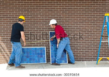 Workers measuring and installing solar electric panels. - stock photo
