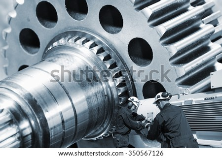 workers, mechanics with machinery, large cogwheels axle in background - stock photo