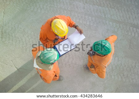 Workers of a copper mine reviewing a sheet - stock photo