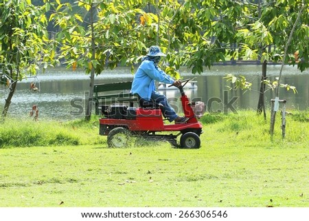 Workers on ride-on lawn mower cutting grass. - stock photo
