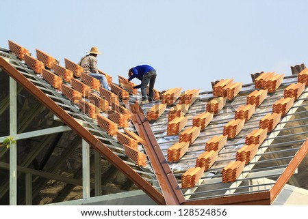 workers on roof - stock photo