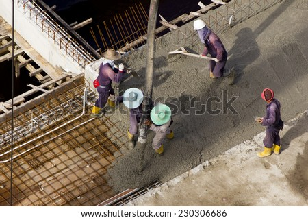 Workers pouring cement as a foundation for a new buildings, Brunei - stock photo