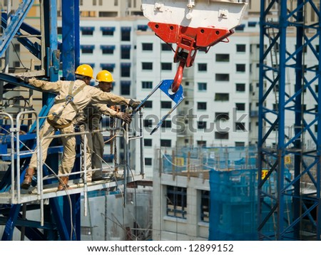 Workers reining in a tower crane's hook during the construction of its height extension - stock photo