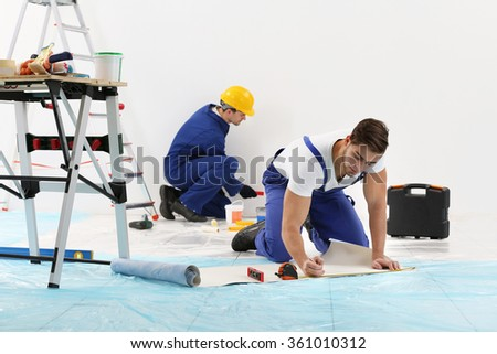 Workers renewing apartment on wall background