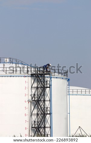 workers standing on oil tank - stock photo