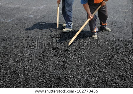 Workers team throw asphalt  with shovels at road construction - stock photo