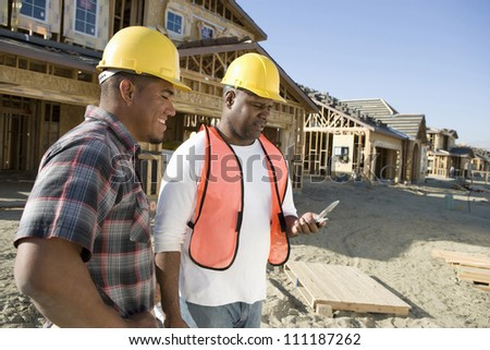 Workers using cell phone at construction site - stock photo