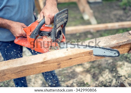 workers using chainsaw cutting and sawing industrial construction wood. Laborer slicing timber - stock photo