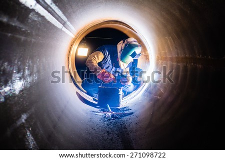 Workers welding work at night in the pipeline. - stock photo