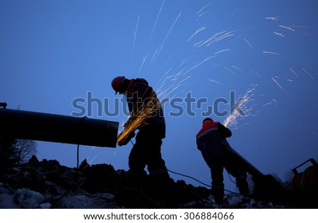 Workers working on the construction of the pipeline - stock photo