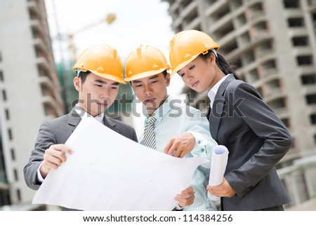 Workgroup of three developers collaborating on site - stock photo
