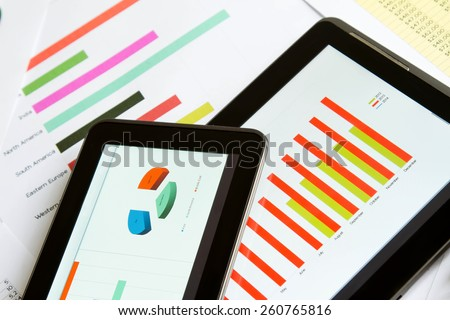 Working, analyzing graphics with the tablet and doing calculations  - stock photo
