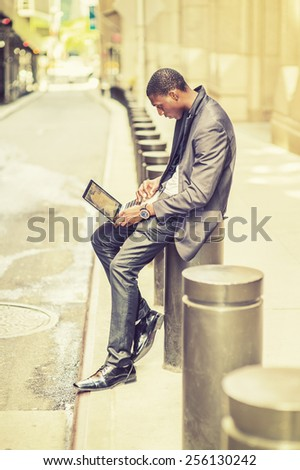Working anywhere, anytime. Young man working on street. A young black college student is sitting outside an office building, typing on a laptop computer, reading, thinking. Retro filtered look. - stock photo