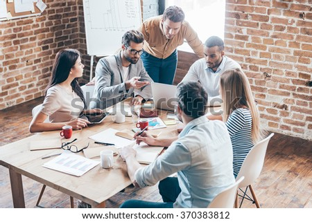 Working as team. Group of six young people discussing something and gesturing while sitting at the table in office - stock photo