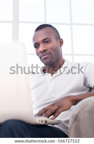 Working at home. Handsome young African man using computer and while sitting on the chair - stock photo