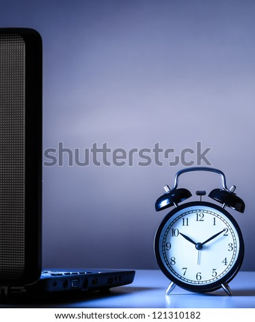 working at night, laptop with clock on table - stock photo