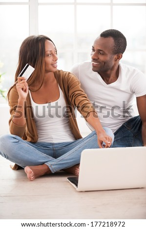 Working at their new tablet. Beautiful young African couple using digital tablet while sitting together on the floor at their apartments  - stock photo