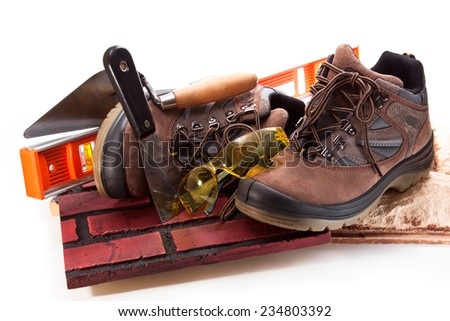 Working boots, tile, trowel, spatula,  goggles  and level on a white background - stock photo
