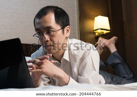 Working businessman sit on bed in hotel. - stock photo