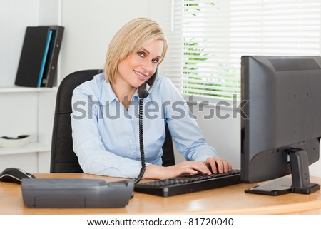 Working businesswoman on the phone while typing looking into the camera in her office