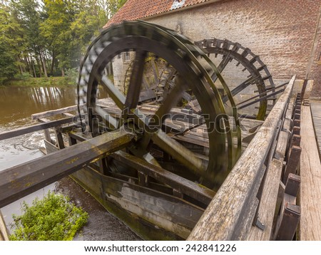 Working Cogwheel driven watermill at Singraven castle in Dinkelland, Netherlands - stock photo