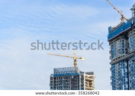 Working crane on a modern office building under construction against blue sky in Singapore. Asian urban development and construction concept. Industrial background - stock photo